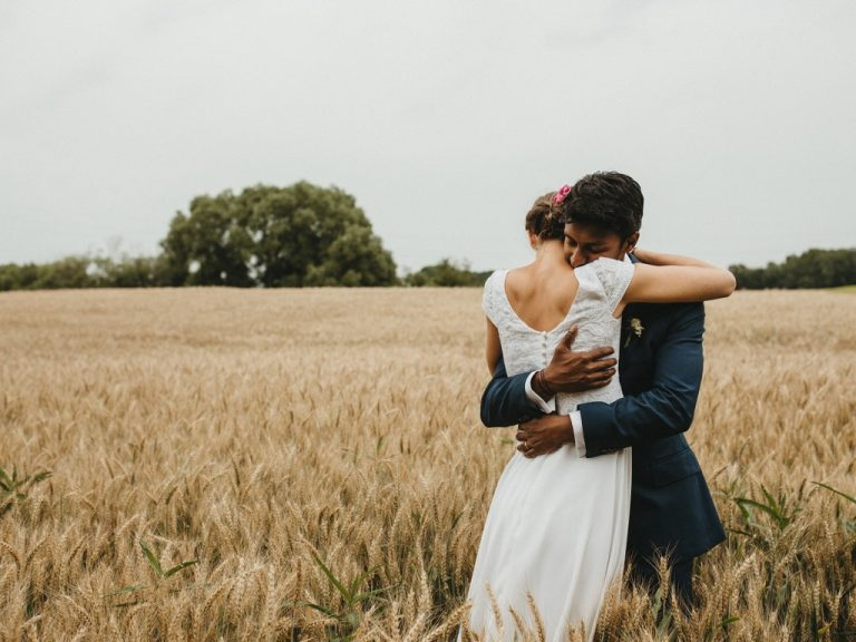 bride-groom-hug-wedding-dress-wheat-field-cloudy-countryside